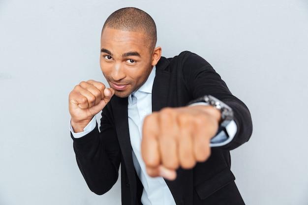 ボクサーの位置に立って、彼の拳を食いしばって戦う準備ができている青年実業家