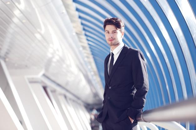 Молодой предприниматель, стоя в коридоре современного офисного здания