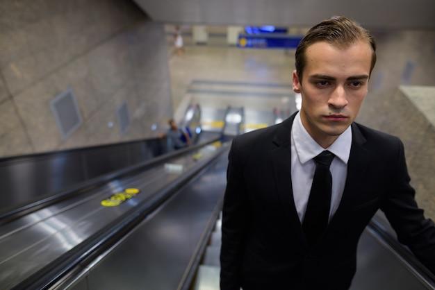 Молодой предприниматель, стоя в эскалаторе на вокзале