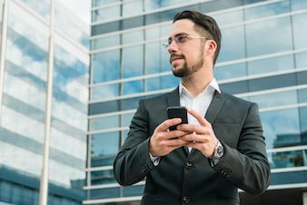 Young businessman standing in front of office building holding mobile phone