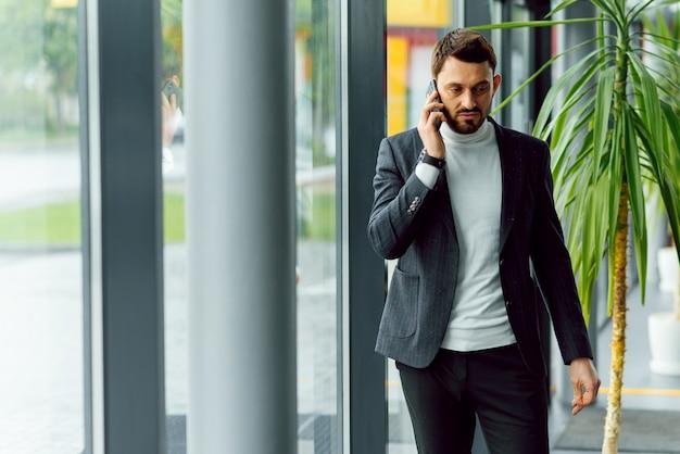 Молодой предприниматель, стоя в офисном зале и разговаривает по телефону
