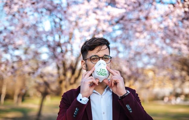 공원에 서서 보호 마스크를 쓴 젊은 사업가. 코로나바이러스, 코비드-19 개념.
