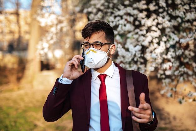 공원에 서서 전화 통화를 하고 보호 마스크를 쓴 젊은 사업가. 건강 관리, 바이러스 보호, 알레르기 보호 개념.
