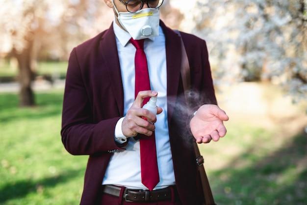 공원에 서서 보호 마스크를 쓰고 알코올로 손을 소독하는 젊은 사업가.
