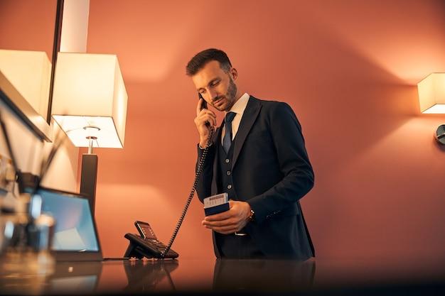 Молодой бизнесмен стоит в зоне бизнес-зала аэропорта и держит в руках паспорт с билетом во время разговора по телефону