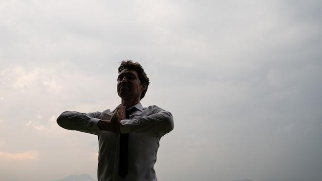 曇り空の下に立って両手で瞑想している青年実業家が胸の前で合流した。