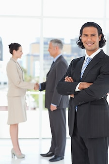 Young businessman standing upright in front of colleagues shaking hands
