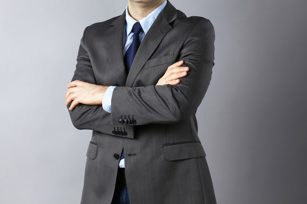 Young businessman standing with arms crossed, in suit