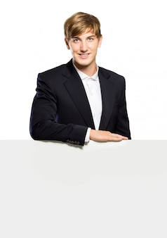 Young businessman standing with a balnk whiteboard , isolated
