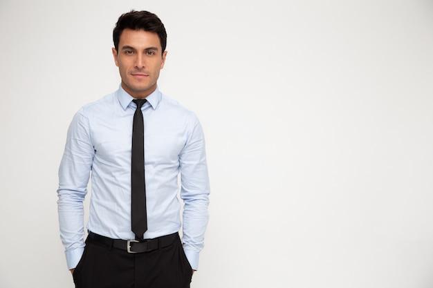 白で隔離されるポケットに手で立っている青年実業家