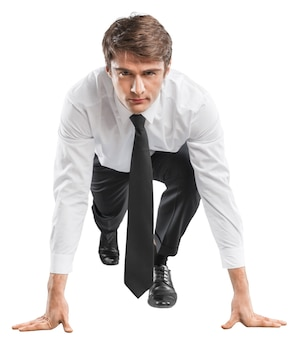 Young businessman in start pose for running on background