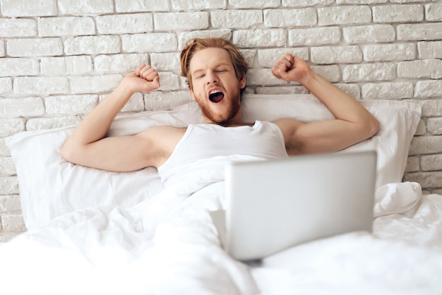 Young businessman stretches in bed