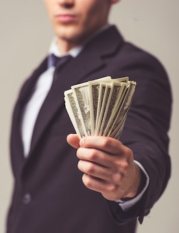 Young businessman in suit holding money