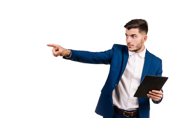 Young businessman in suit pointing seriously while holding tablet