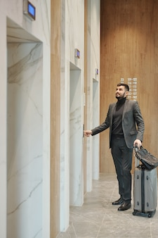 Young businessman in suit pushing button on the wall while standing by one of elevator doors in hotel