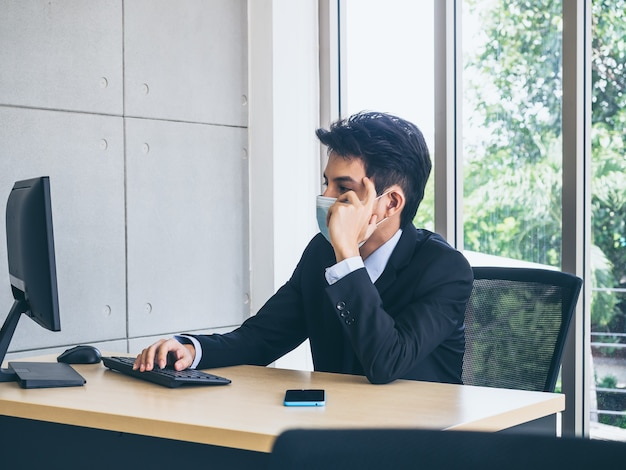 Young businessman in suit wearing protective face mask working on computer and thinking with strain with tired face with smartphone on desk in office near huge glass window.