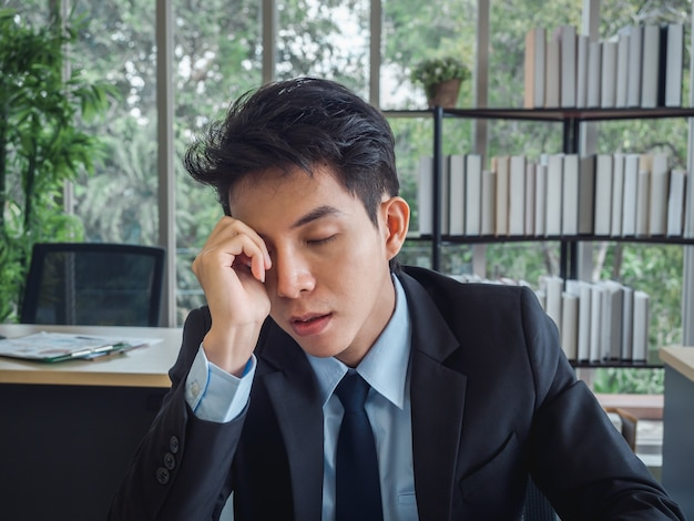 Young businessman in suit with problems, tired, stressed and sad boring sitting with absent-minded on his desk in office.