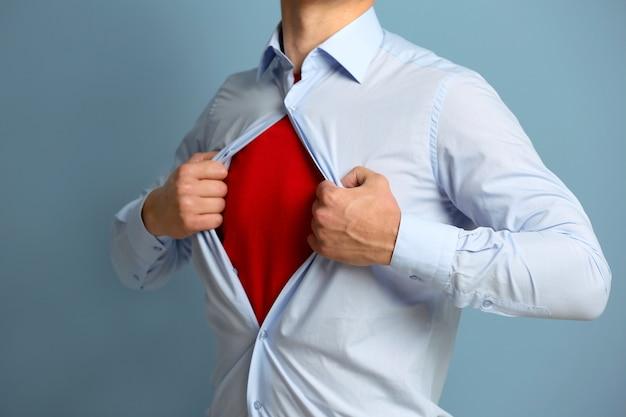 Молодой бизнесмен супер герой на синей поверхности