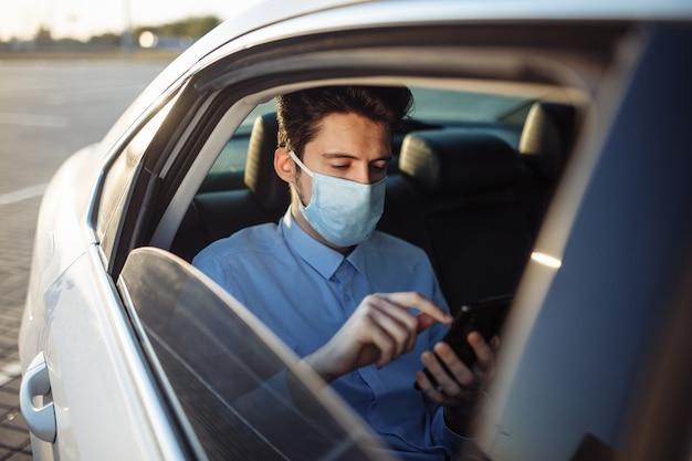 젊은 사업가 택시를 타고 멸균 의료 마스크를 쓰고 자신의 휴대 전화에 보인다. 사회적 거리 개념.
