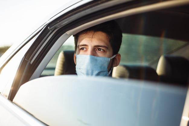 젊은 사업가 택시를 타고 살 균 의료 마스크를 쓰고 차 창 밖으로 보인다. 사회적 거리 개념.