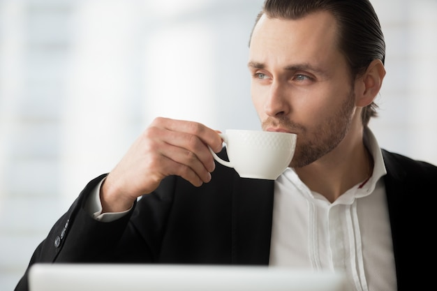 Young businessman takes coffee-break at workplace