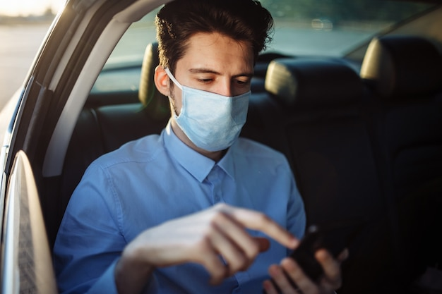 Young businessman takes a taxi and looks into his cell phone wearing sterile medical mask. social distance concept.