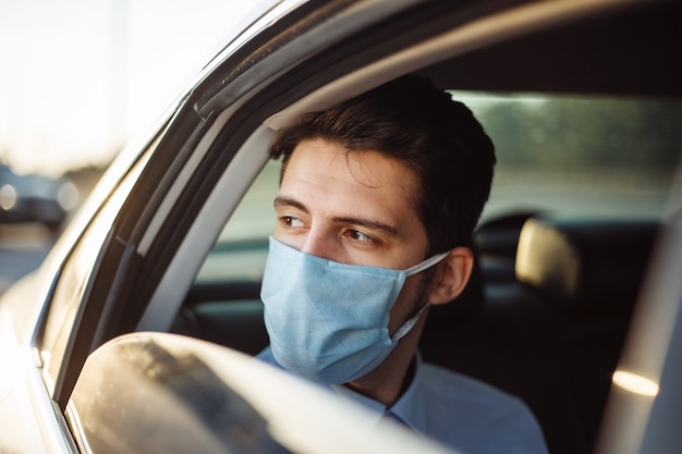 Young businessman takes a taxi and looks out of the car window wearing sterile medical mask. social distance concept.