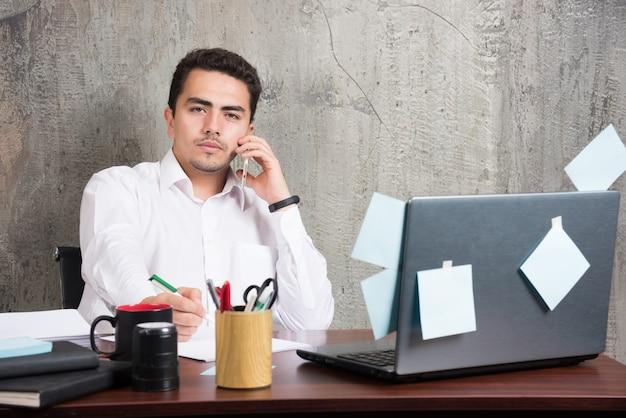 Giovane imprenditore parlando di questioni serie alla scrivania in ufficio.