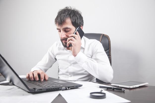 Молодой предприниматель разговаривает по мобильному телефону и с помощью ноутбука.