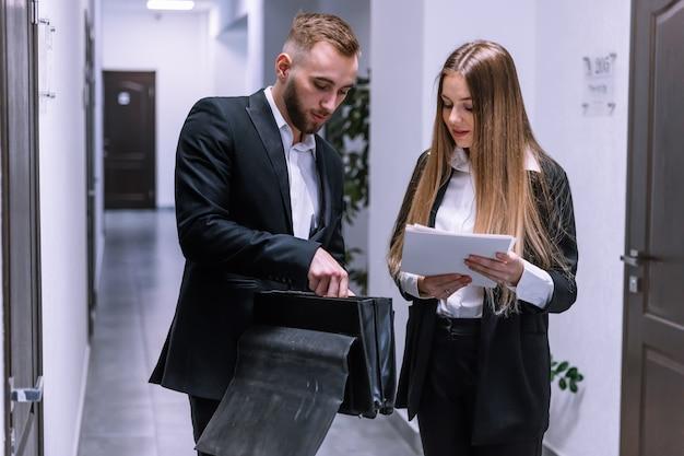 彼らが廊下に立っている間、彼のブリーフケースから文書を話し、彼の同僚に見せている青年実業家