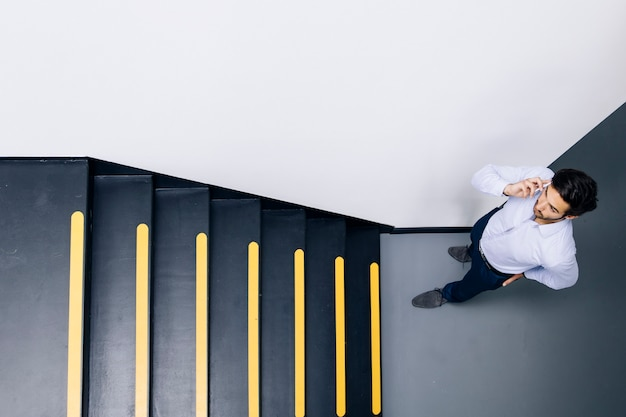 Young businessman talking on mobile phone and climbing on the stairs in office