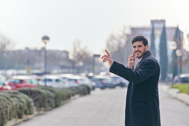 彼の手を上げることによってタクシーを呼び出している間彼の携帯電話で話している青年実業家