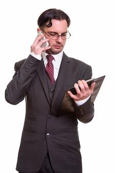 クリップボードを読みながら携帯電話で話している青年実業家