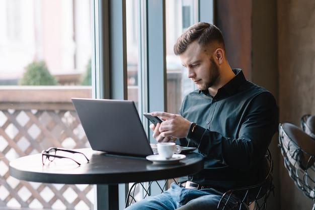 カフェでノートパソコンで作業しながら携帯電話で話している青年実業家