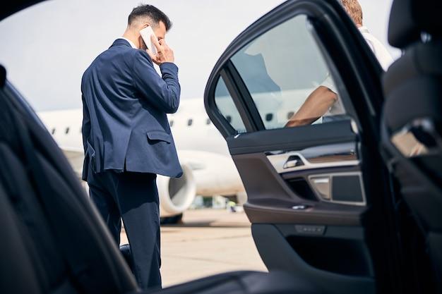 開いたドアでタクシーのそばに立って電話で話している青年実業家が飛行機から迎えに行く