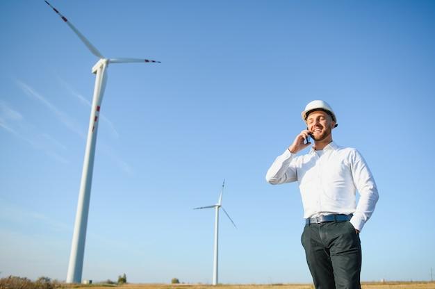 풍력 터빈 분야, 녹색 에너지 개념에서 스마트 전화를 사용하여 관리자와 이야기하는 젊은 사업가