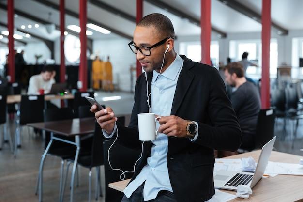 Молодой бизнесмен текстовых сообщений на смартфоне и держа чашку в офисе