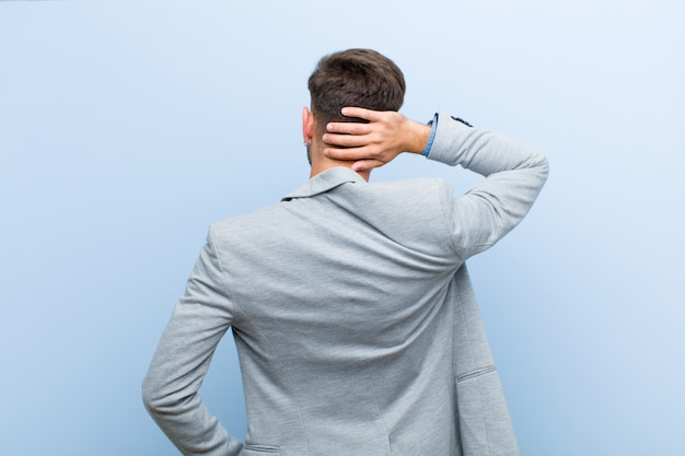 Young businessman thinking or doubting, scratching head, feeling puzzled and confused, back or rear view against blue background