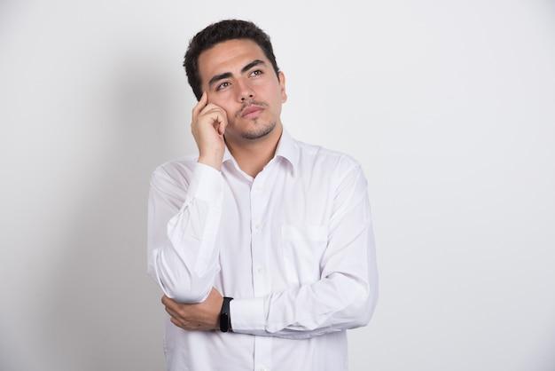 Giovane imprenditore pensando intensamente su sfondo bianco.