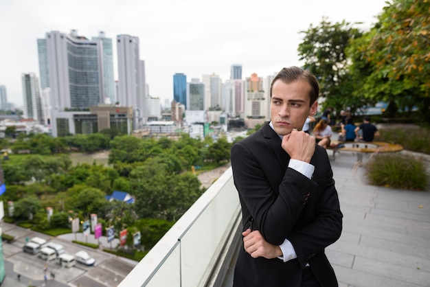 Young businessman thinking outdoors in city with rooftop view