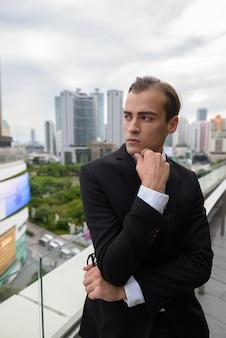屋上ビューと街の屋外で考える青年実業家