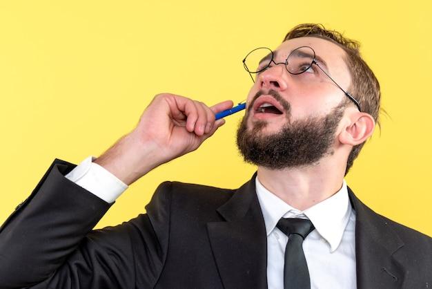 Penna di pensiero del giovane uomo d'affari sulla guancia su colore giallo