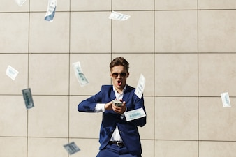 Young businessman throughs around dollars and dances on the street