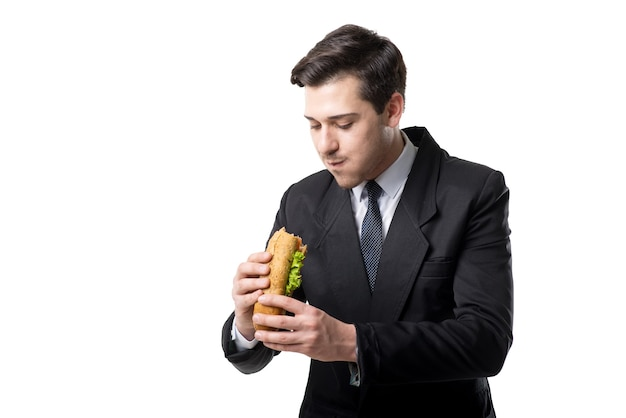 Young businessman in tie and black suit eats hot dog, isolated on white
