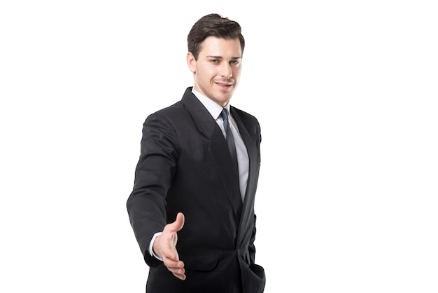 Young businessman in tie and black suit extends his hand, isolated on white