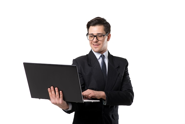 Young businessman in tie and black suit using laptop, isolated on white
