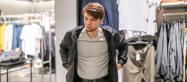 Young businessman try on new jacket in the store