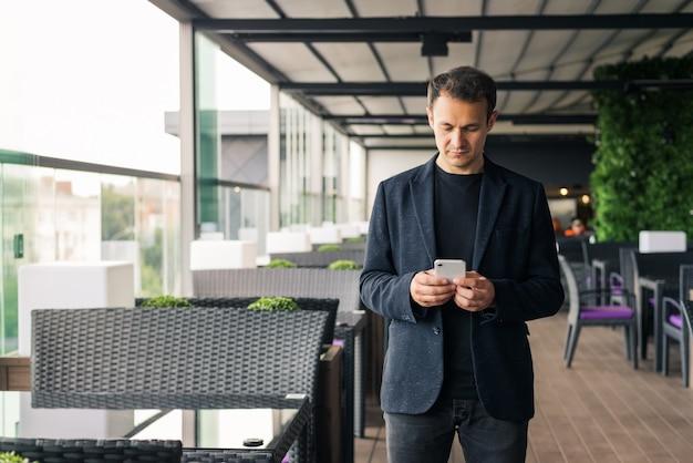 カフェで彼のスマートフォンで入力する若いビジネスマン
