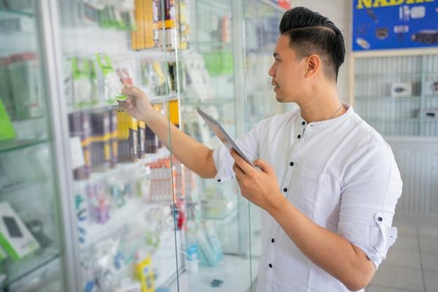 ガラスの陳列ケースに付属品のタイトな在庫を持つタブレットを使用して青年実業家