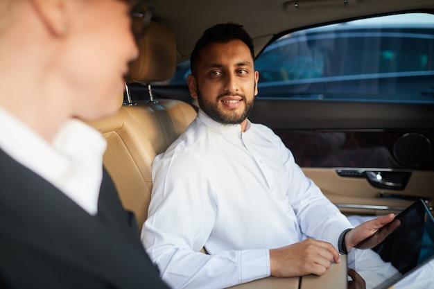그들은 차에 앉아있는 동안 디지털 태블릿을 사용하고 그의 동료와 온라인 프레젠테이션을 논의하는 젊은 사업가